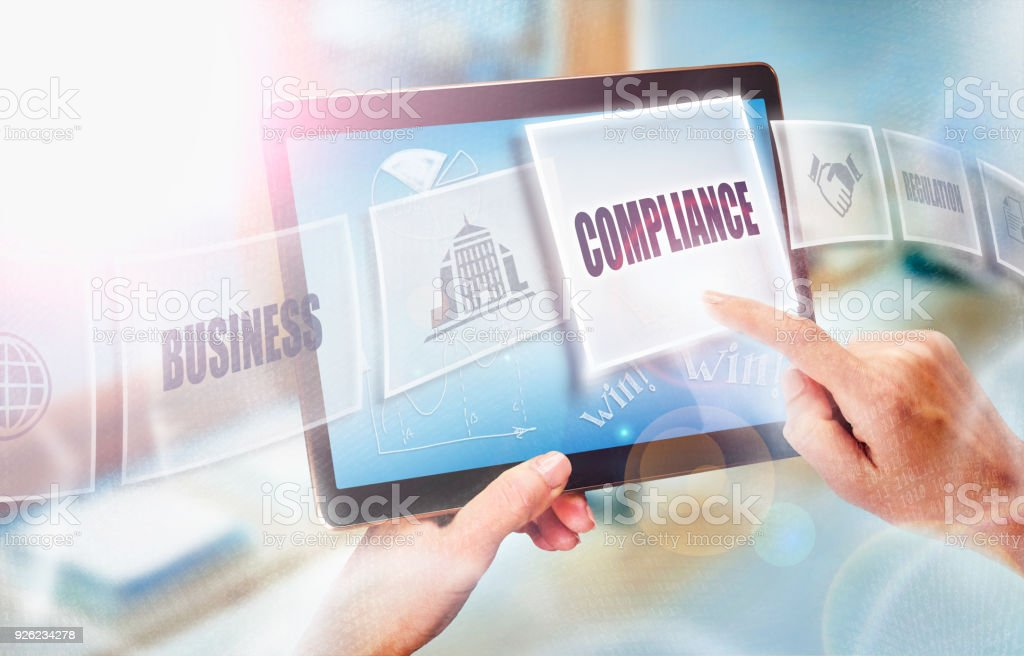 A businesswoman selecting a Compliance business concept on a futuristic portable computer screen. stock photo