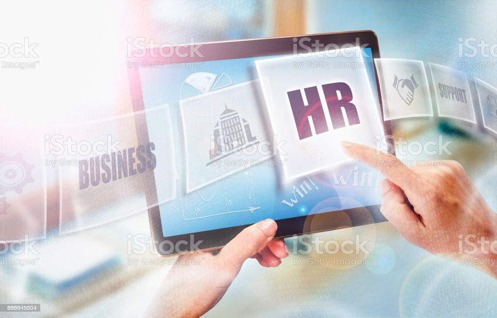 A businesswoman selecting a HR business concept on a futuristic portable computer screen. stock photo