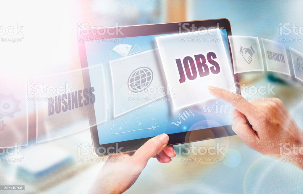 A businesswoman selecting a Jobs business concept on a futuristic portable computer screen. stock photo