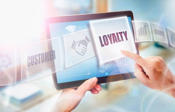a businesswoman selecting a loyalty business concept on a futuristic portable computer screen. - fedeltà foto e immagini stock
