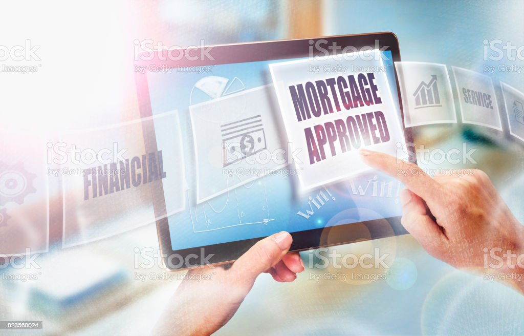 A businesswoman selecting a Mortgage Approved business concept on a futuristic portable computer screen. stock photo