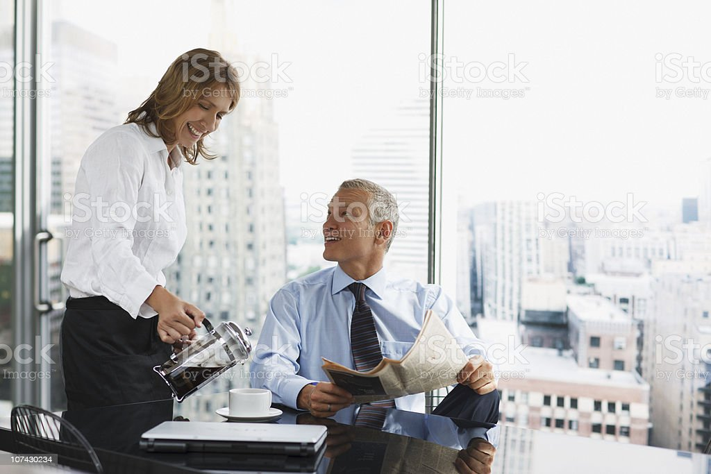 Businesswoman serving co-worker coffee in office stock photo