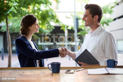 istock Businesswoman shaking hands with businessman at counter 648791434