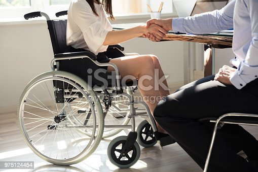 1144373653 istock photo Businesswoman Shaking Hands With Her Colleague 975124454