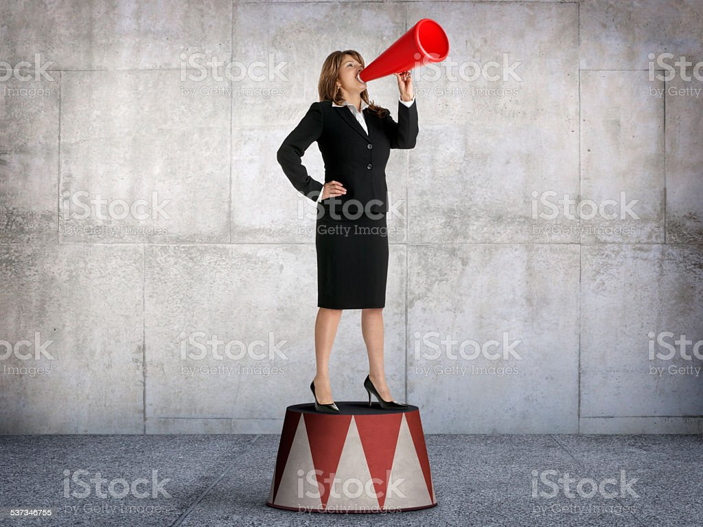 Businesswoman Shouting From Pedestal stock photo