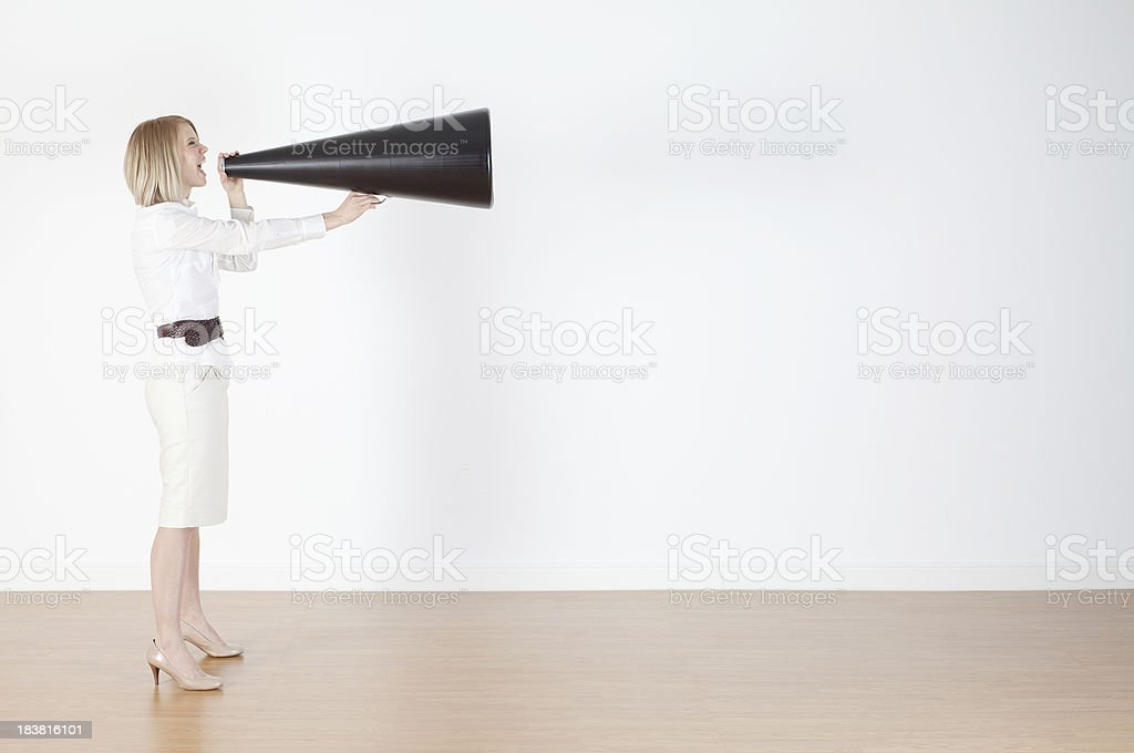 Businesswoman shouting into a bullhorn royalty-free stock photo