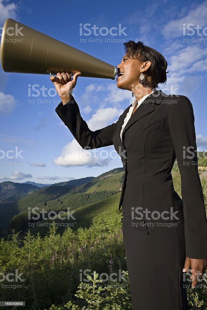 Businesswoman Shouting With Megaphone In Mountains stock photo