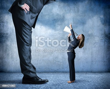 A businesswoman shouts through a megaphone and points up towards a much larger businessman who is standing over her.