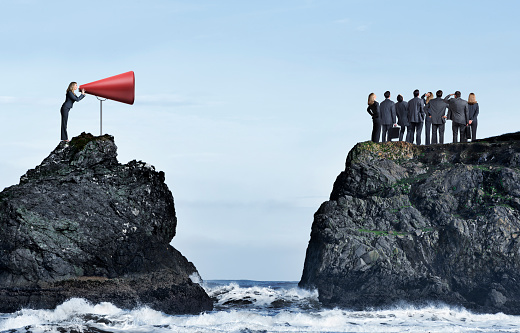 A businesswoman, standing on top of a rocky cliff, shouts through a very large red megaphone toward a group of business people who stand on an opposite cliff and aren't paying attention to her.