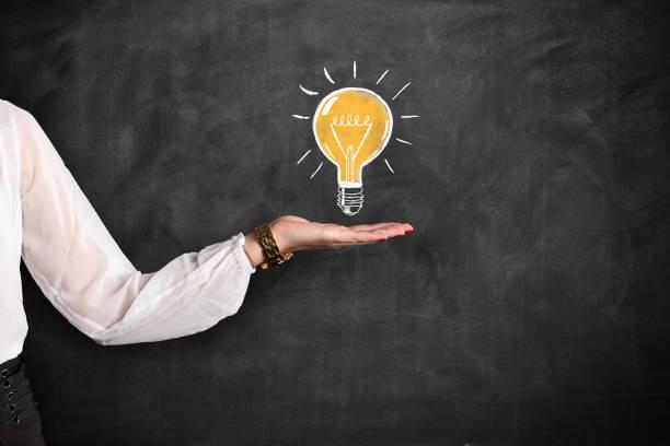 Geschäftsfrau zeigt Kreide ziehen Glühbirne auf Tafel – Foto