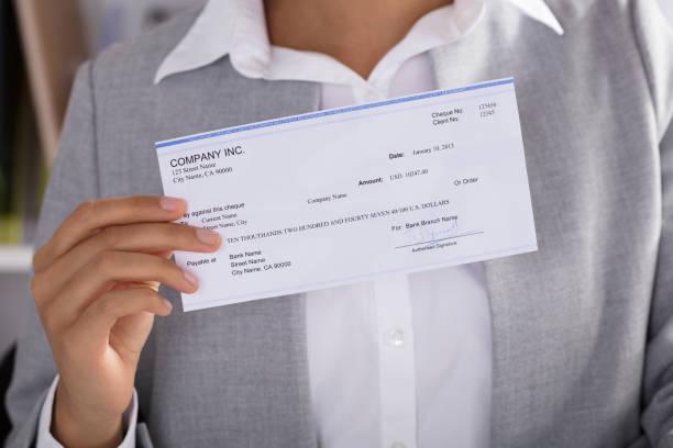 mujer de negocios mostrando cheque - accesorio financiero fotografías e imágenes de stock