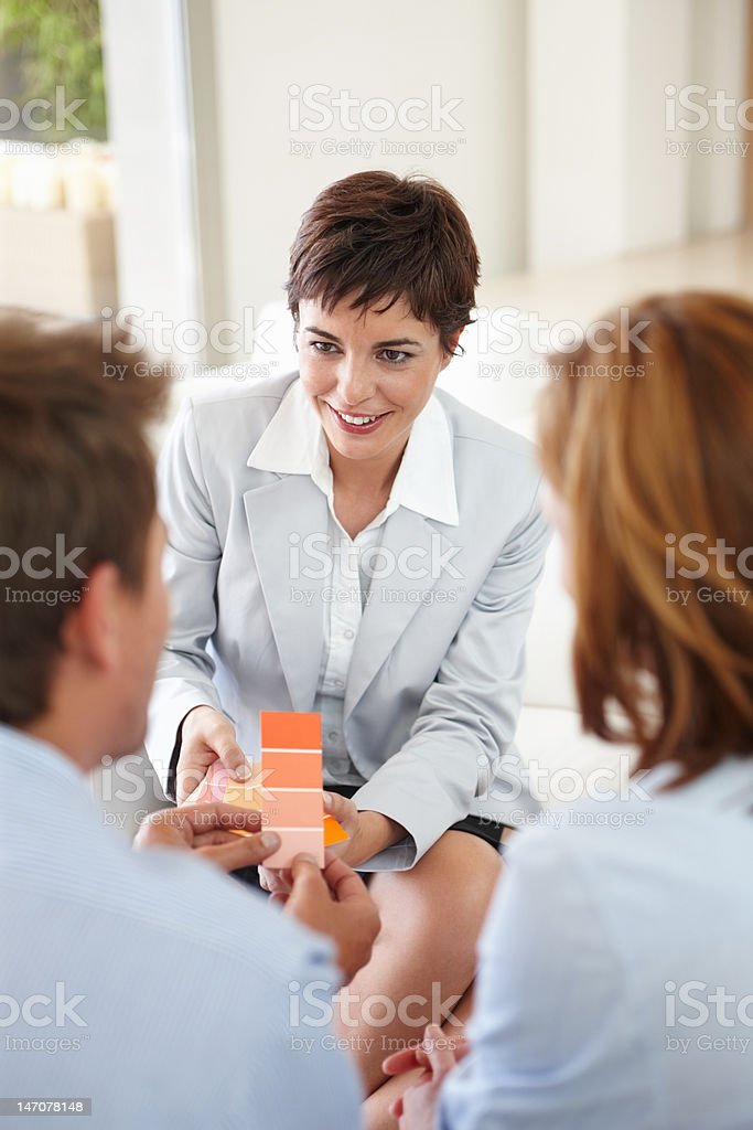 Businesswoman showing color pads to a young couple royalty-free stock photo