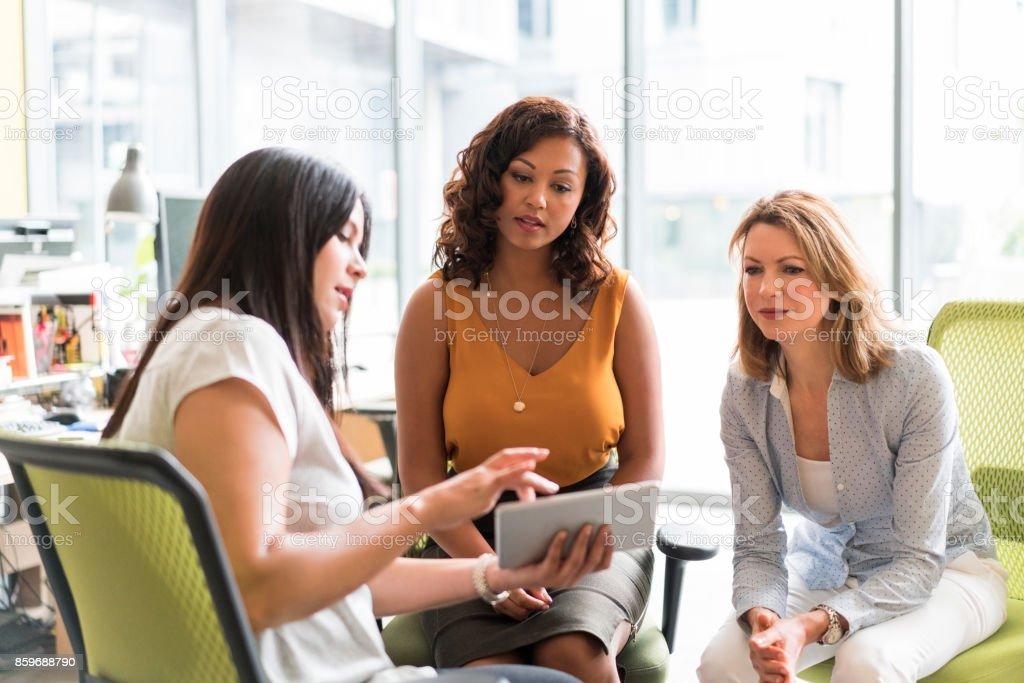 Geschäftsfrau zeigt digital-Tablette an Kollegen – Foto