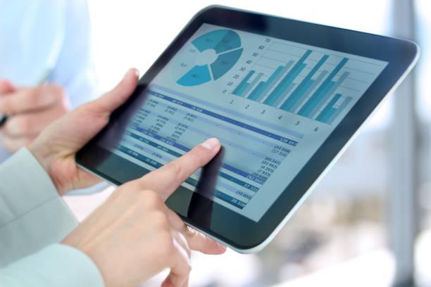 Geschäftsfrau zeigt Grafiken mit dem Finger am digitalen Tablet – Foto