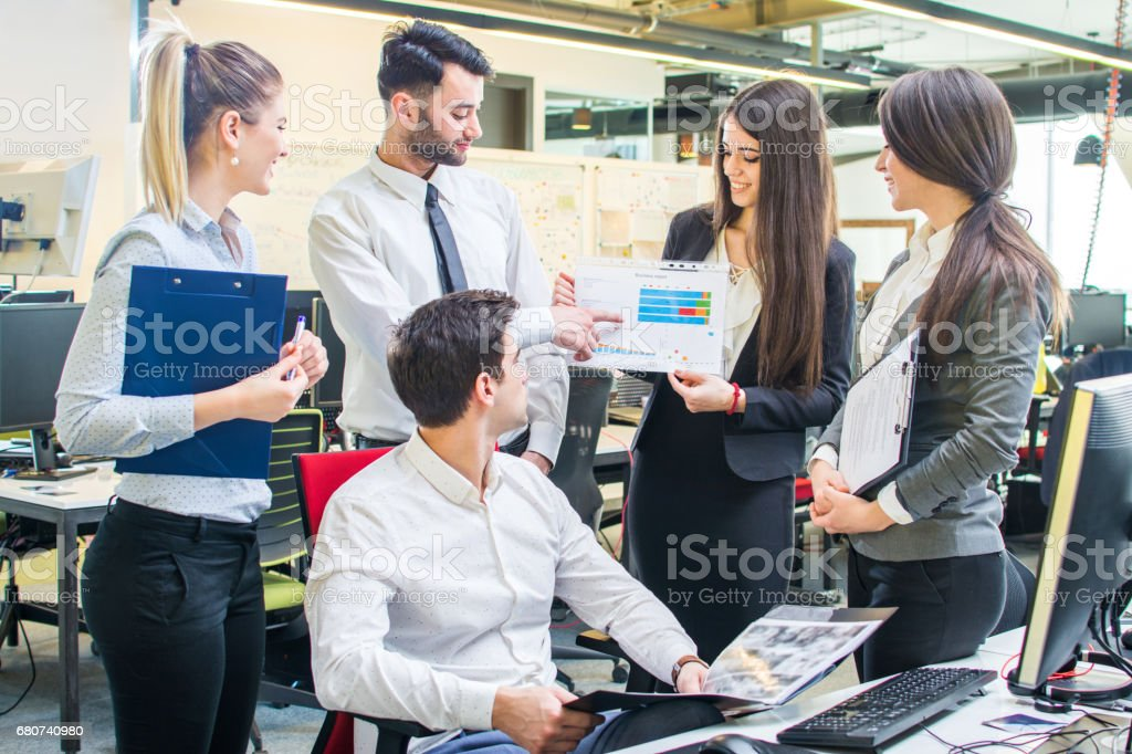 Businesswoman showing graphs of company progress to her colleagues at meeting in the office. stock photo