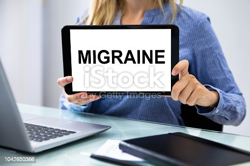 Close-up Of A Businesswoman's Hand Showing Migraine Word On Digital Tablet