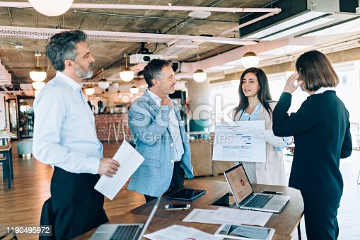 Businesswoman showing sales leads to coworkers