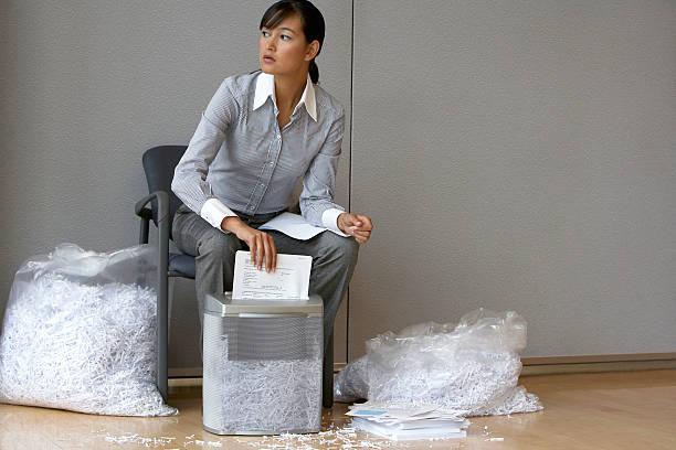 Businesswoman shredding documents stock photo