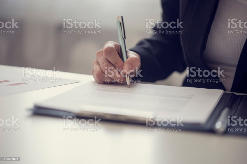 Businesswoman signing a contract or document stock photo