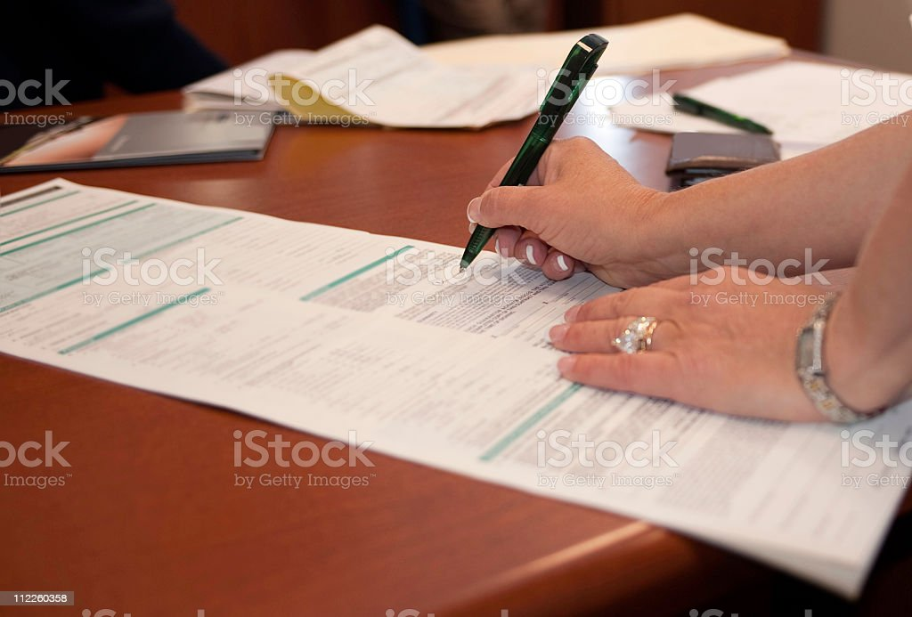 Businesswoman signing a form stock photo