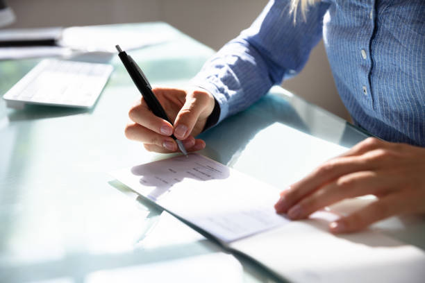 Businesswoman Signing Cheque stock photo