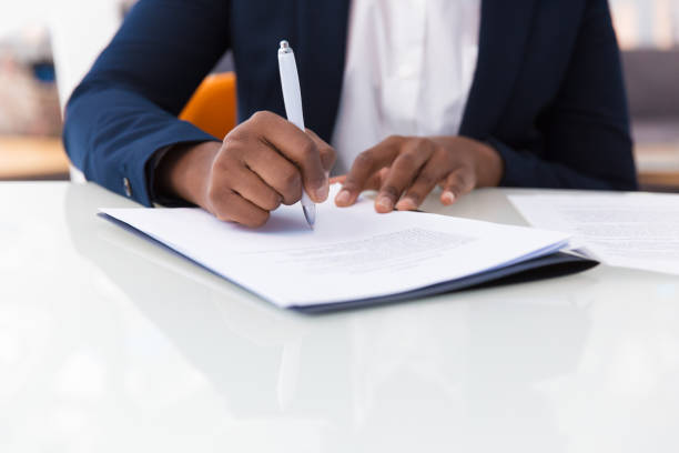 Businesswoman signing contract Businesswoman signing contract. African American business woman sitting at table in office, holding pen and writing in document. Legal expertise concept agreement stock pictures, royalty-free photos & images