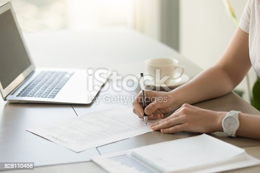 istock Businesswoman signing paper at workplace, executive putting signature on contract 828110458
