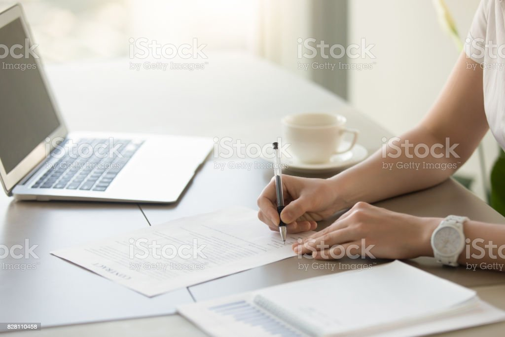Businesswoman signing paper at workplace, executive putting signature on contract stock photo