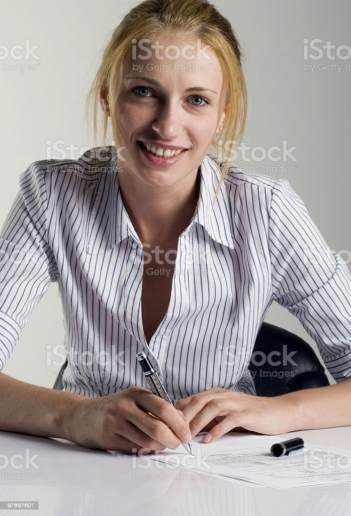 Businesswoman signing papers and smiling royalty-free stock photo