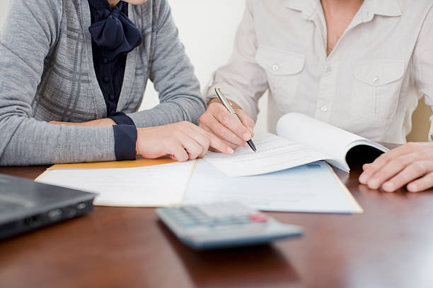 businesswoman signing paperwork - mortgages and loans stock pictures, royalty-free photos & images