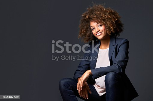Smiling businesswoman sitting against gray background. Portrait of beautiful female executive with curly short hair. Confident professional wearing formals.