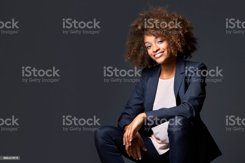 Businesswoman sitting against gray background stock photo
