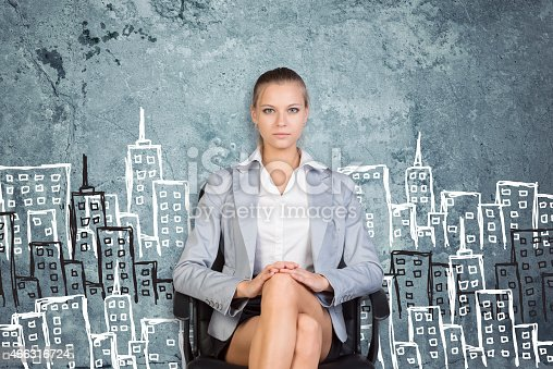 istock Businesswoman sitting against wall with sketch of city 466316724