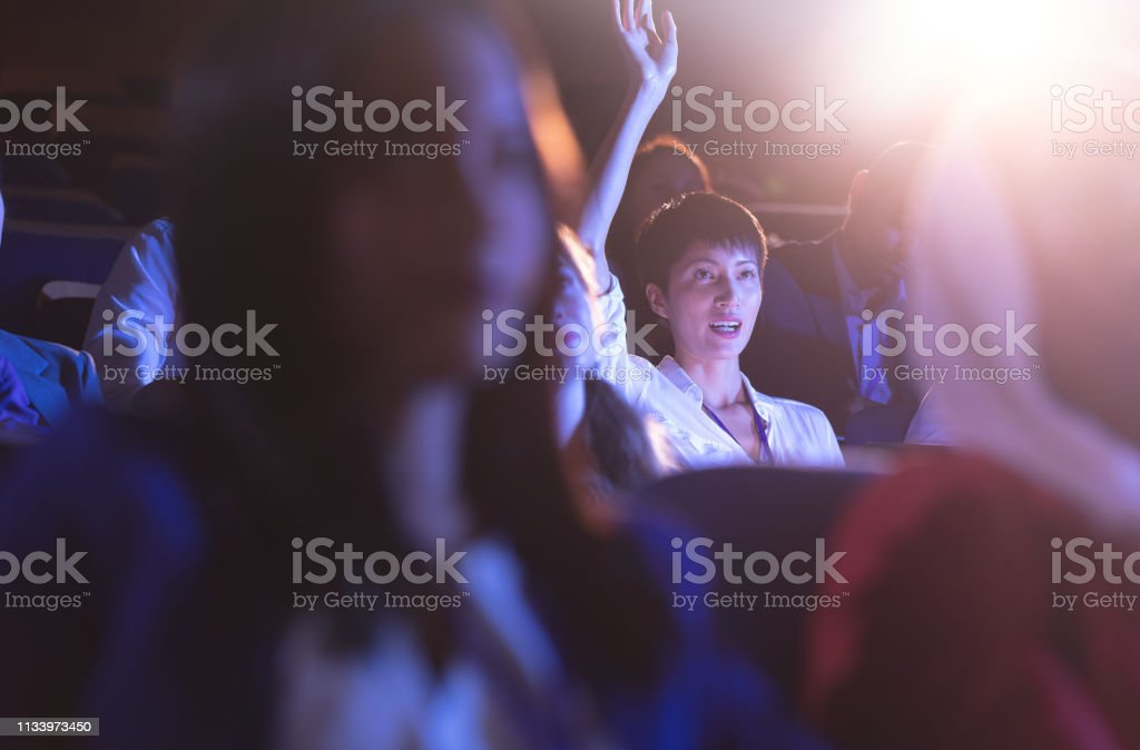 Front view of beautiful Asian businesswoman sitting and raising hand...