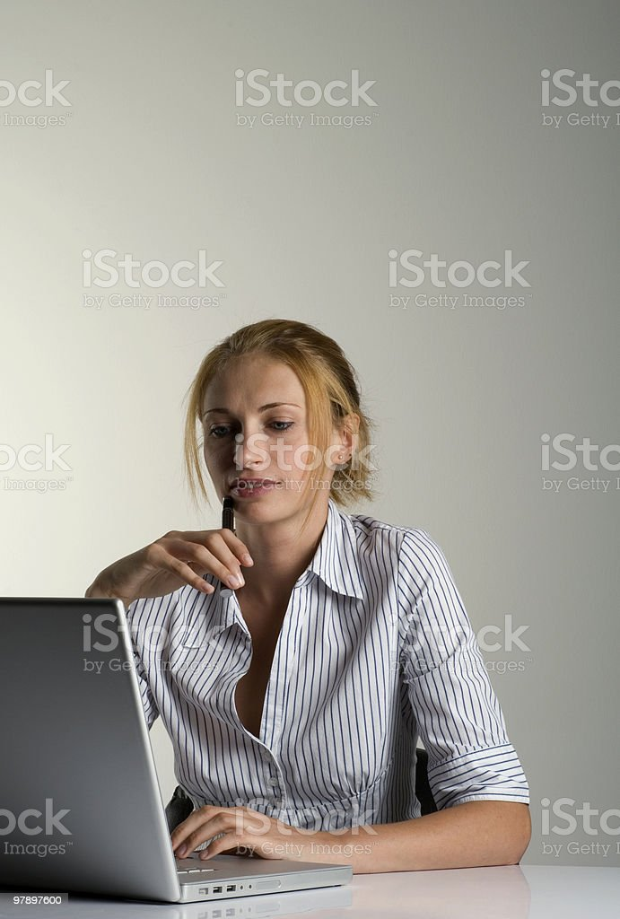 Businesswoman sitting and working on her laptop, close-up royalty-free stock photo