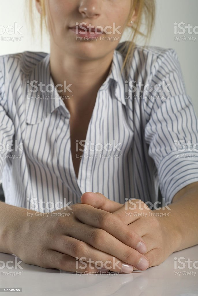 Businesswoman sitting at a table with her hands clasped royalty-free stock photo