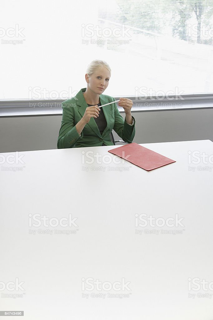 Businesswoman sitting at conference table royalty-free stock photo