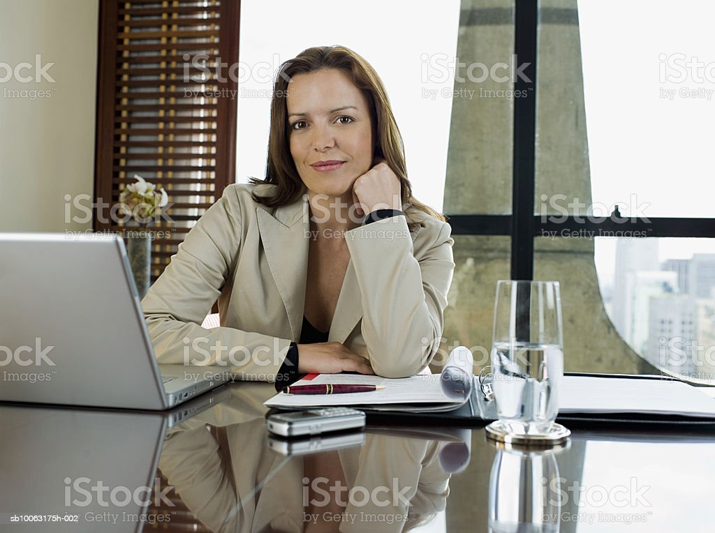 Businesswoman sitting at desk, smiling, portrait royalty-free stock photo