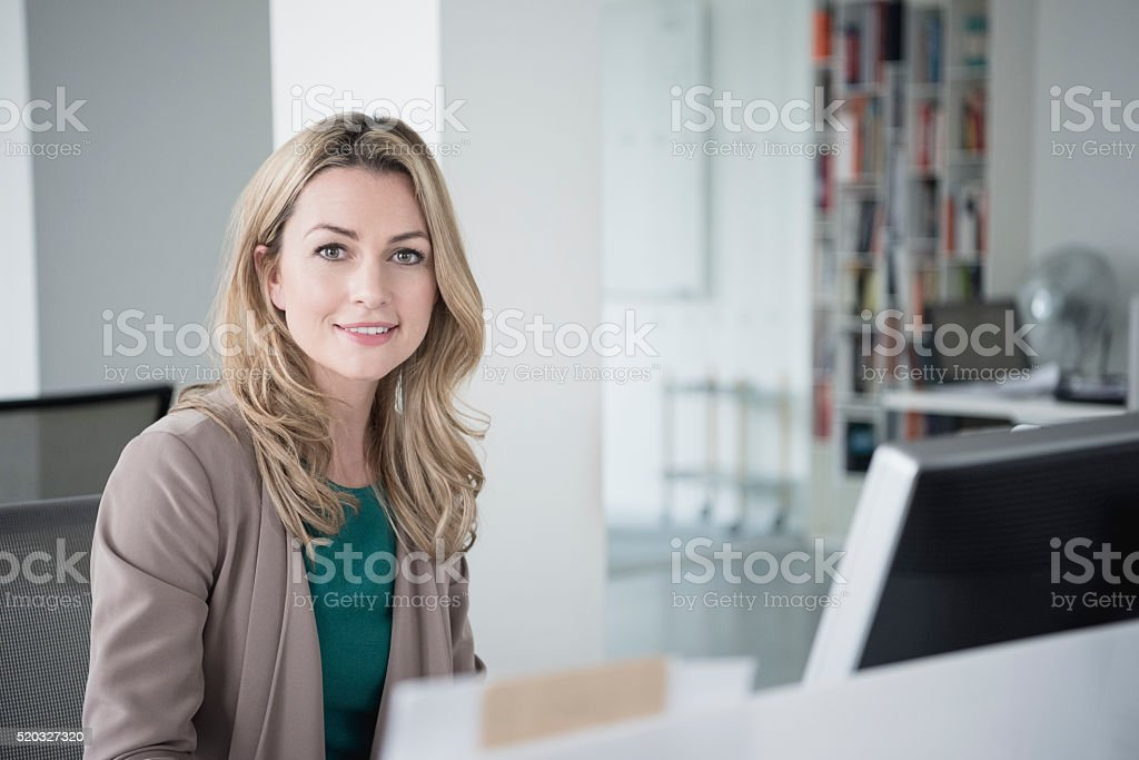 Businesswoman sitting at desk with computer smiling towards camera stock photo