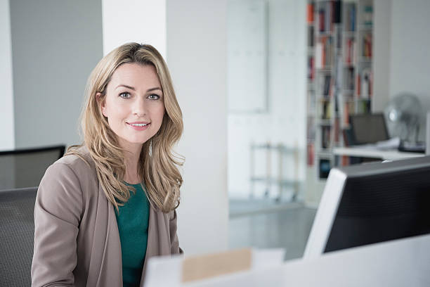 businesswoman sitting at desk with computer smiling towards camera - white collar worker stock photos and pictures