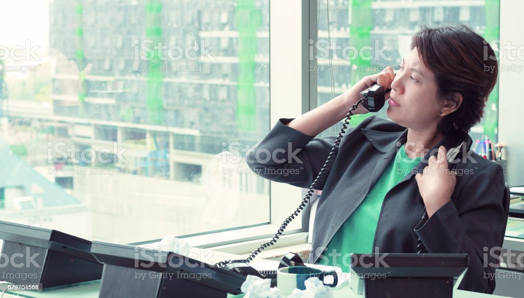Businesswoman Sitting at her Desk Answering a Telephone Call from a Custome – Foto