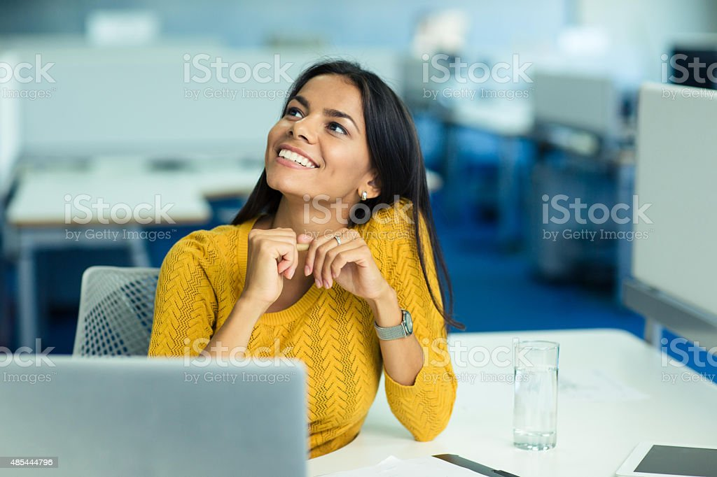 Businesswoman sitting at her workplace in office Portrait of a happy businesswoman sitting at her workplace in office and looking up 2015 Stock Photo