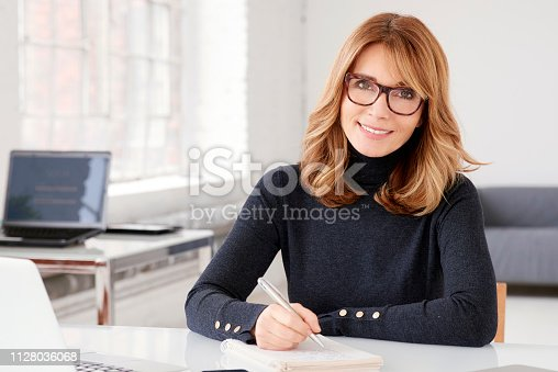 istock Businesswoman sitting at office desk and doing some paperwork 1128036068