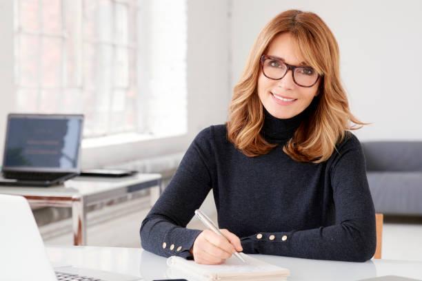 Geschäftsfrau am Schreibtisch sitzen und einigen Papierkram zu tun – Foto