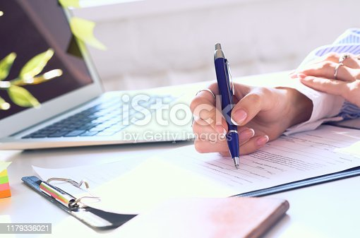 Businesswoman sitting at office desk signing a contract or making notes closeup.
