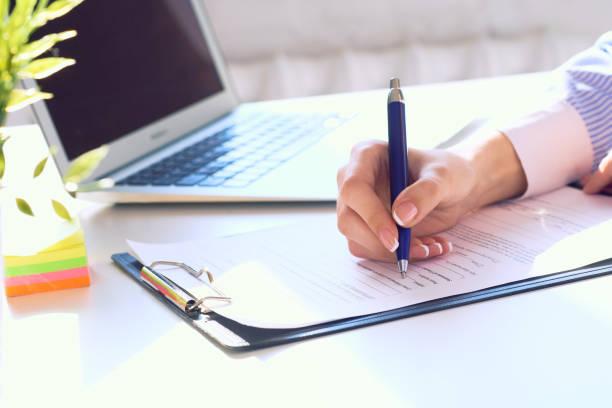 Geschäftsfrau, die am Schreibtisch sitzt und einen Vertrag unterschreibt oder Notizen macht. – Foto