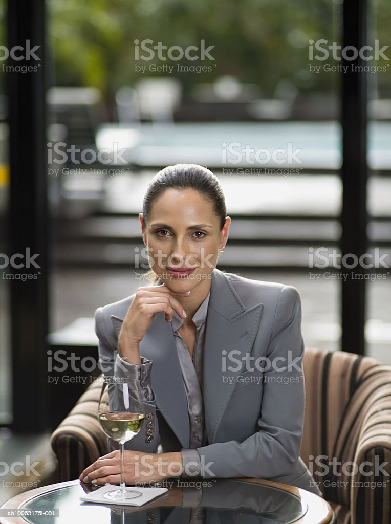 Businesswoman sitting at table with wine, smiling, portrait royalty-free stock photo