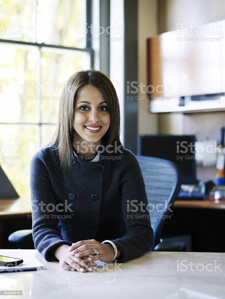 Businesswoman sitting behind desk, smiling royalty-free stock photo