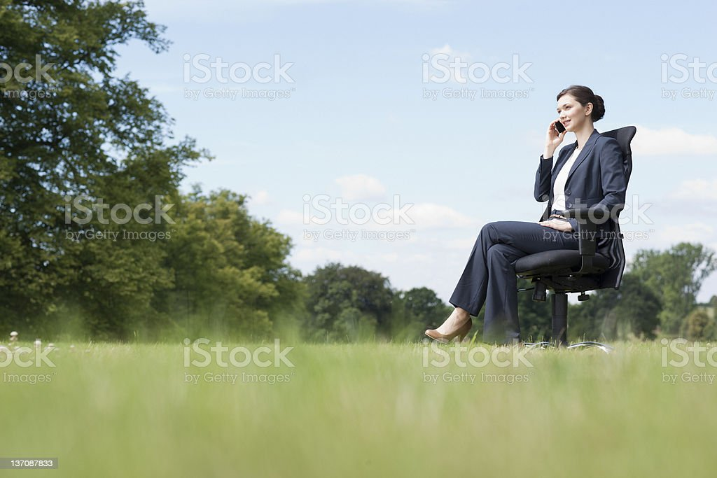 Businesswoman sitting in chair talking on cell phone outdoors stock photo
