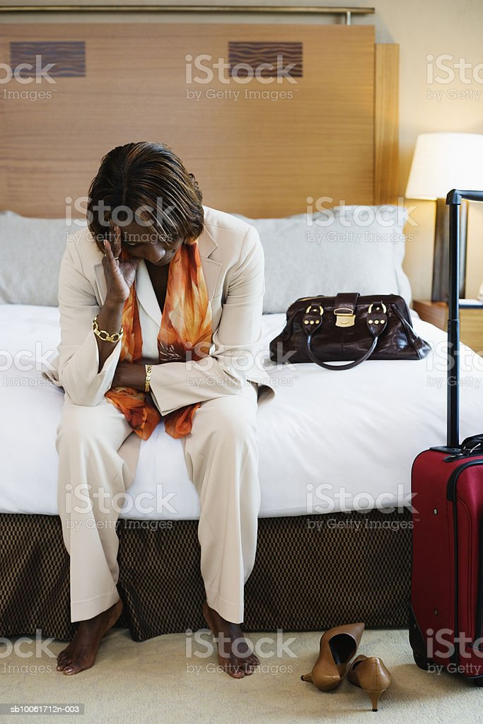 Businesswoman sitting in hotel bedroom with head in hands foto royalty-free